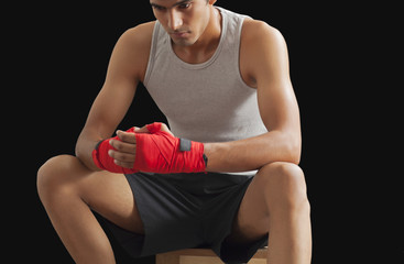 Thoughtful male boxer sitting against black background