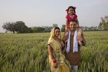 Portrait of rural Indian family with father carrying daughter on shoulders
