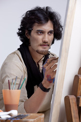 Handsome artist focusing on painting