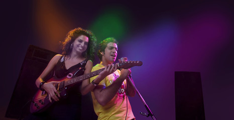 Man singing while a woman plays the guitar