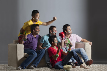 Excited male friends cheering out while watching boxing match together at home