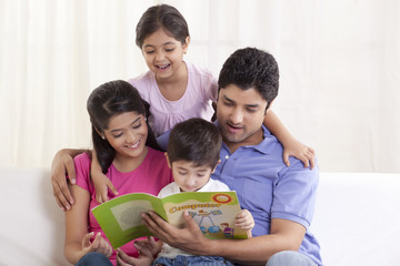 Happy family looking at book