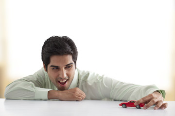Handsome businessman playing with car model