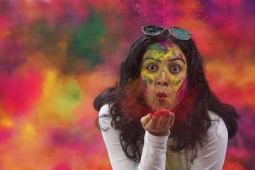 Portrait of an Indian Woman celebrating Holi by blowing Holi powder