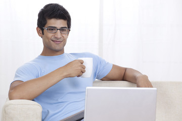 Young Indian man looking at laptop while having coffee