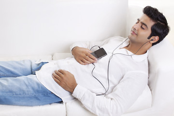 Handsome young man lying on sofa while listening to music