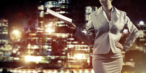 Close of businesswoman against night cityscape background and te