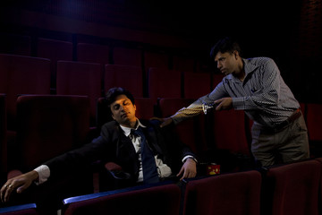 Cinema hall attendant waking a sleeping man