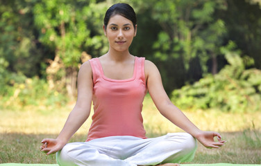 Portrait of young woman in lawn sitting in lotus position