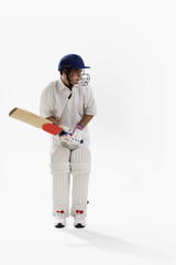 Young man playing cricket isolated over white background