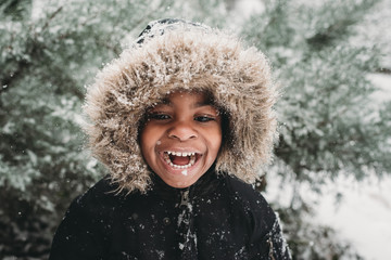 Happy boy standing outdoors in snow during winter