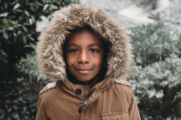 boys smiles sweetly in winter coat