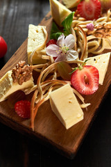 Pieces of cheese on a board with vegetables hd