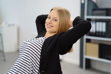 junge mitarbeiterin lehnt sich zufrieden zurück