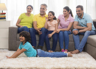 Happy family sitting together on sofa looking away