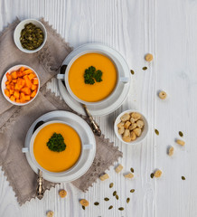 Pumpkin cream soup with croutons, raw fresh pumpkin pieces  and herbs on a white rustic wooden background