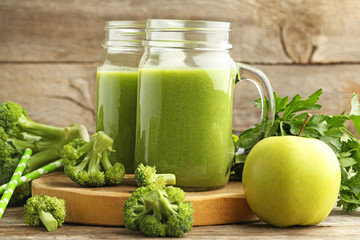 Bottles of juice with broccoli and apple on grey wooden table