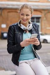 frau mit mobiltelefon und kopfhörern in der stadt