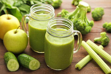 Bottles of juice with broccoli, celery and cucumber on brown wooden table