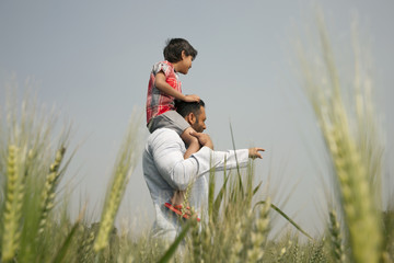 Man pointing at something while carrying little boy on shoulders