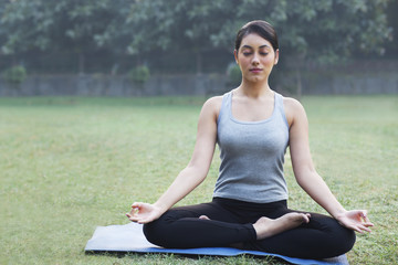 Pretty young woman meditating in park