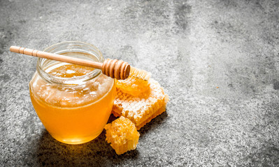 Wall Mural - Fresh honey in jar with wooden spoon.