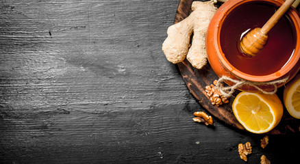 Wall Mural - Honey background. Honey in pot with ginger and lemon.