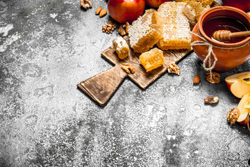 Wall Mural - Honey background. Honey in pot with apples and nuts.