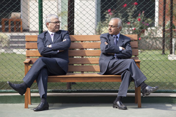 Senior male business executives staring at each other while sitting arms crossed on bench in tennis court