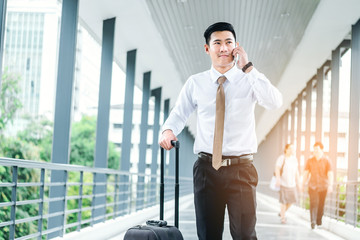 Professional businessman Travel using smartphone talking on his phone smiling happy outside walking inside in airport