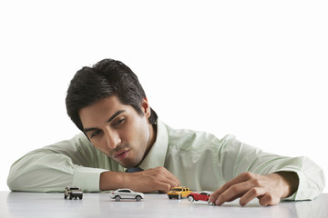 Happy male executive playing with model car