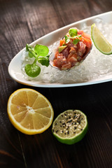 Delicious red fish in the shells of shellfish. With lemon and lime jpg