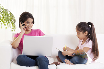Young woman looking at daughter while talking on cell phone
