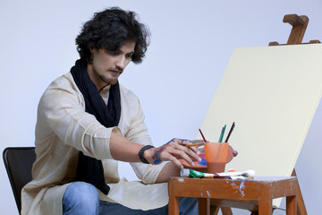 Young artist sitting near easel against colored background