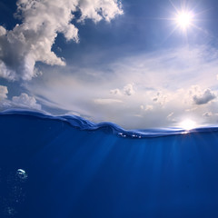 Aquatic Marine Scenery With Bright sun on the sky. White clouds. Ocean Wave divided by waterline.  Air bubbles and sun rays underwater