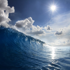 Blue Ocean Wave moving to a shore. Bright Day with sun and white puffy clouds on the sky