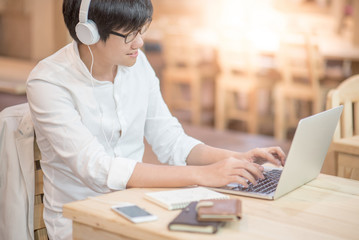 Young Asian happy man with headphones listening to music and working on modern laptop computer in vintage interior workplace, gadget lifestyle and online learning concepts