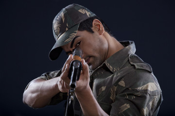 Young soldier aiming gun
