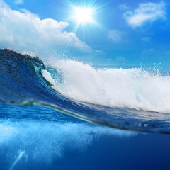 ocean-view seascape landscape Big surfing ocean wave splitted by waterline with slightly cloudy sky and the sun