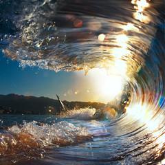 sunset sea curly breaking wave shining in sunlight