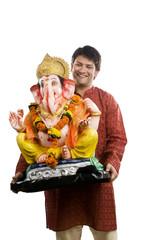 Man carrying a Ganesh idol