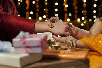 Close-up of a woman tying rakhi on her brother's hand