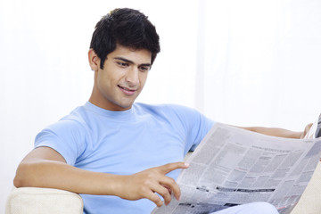 Young Indian man reading newspaper