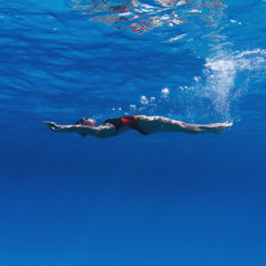 Professional female swimming on her back underwater in blue with air bubbles under water surface