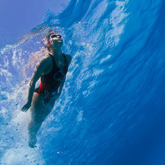 Professional female swimming in blue with air bubbles under water surface