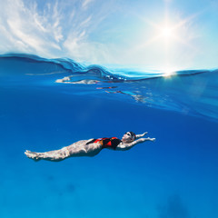 Female professional swimmer swimming on back under waterline with sunshine above