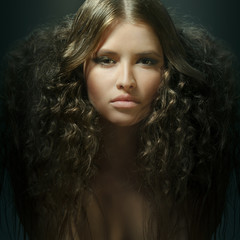 portrait of beautiful young model with creative curly hairstyle looking into camera