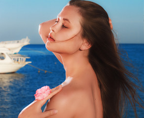Morning on sea beach. Beautiful girl with closed eyes holding pink flower in front of seaview