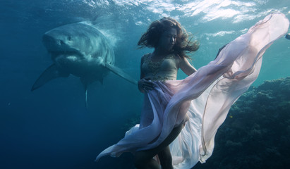 Great white shark approaching a drowning underwater model in pink dress