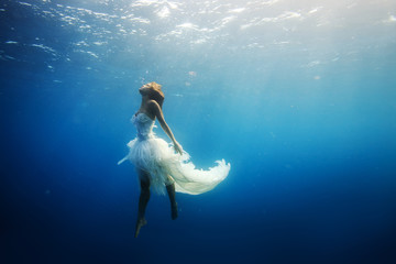 Drawning girl in white dress in deep blue ocean. Underwater shot